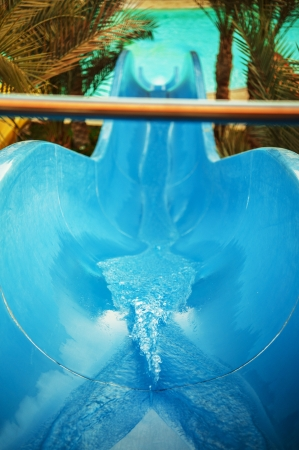 Blue water slide at aquapark in resort beach location. photo