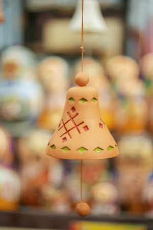 Small earthen bell hanging on string. photo