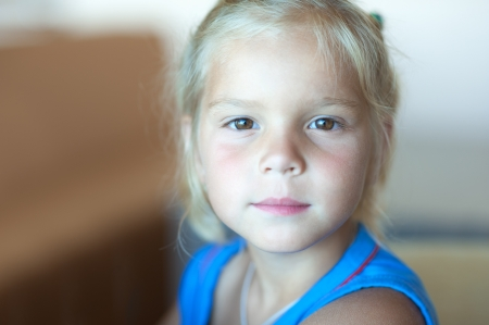 Portrait of pretty little girl in blue dress close-up.