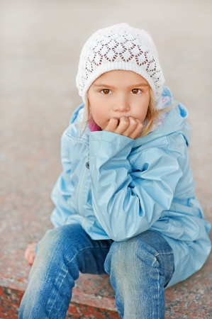 Beautiful little girl in white hat and jacket around school building. Stock Photo - 21140585