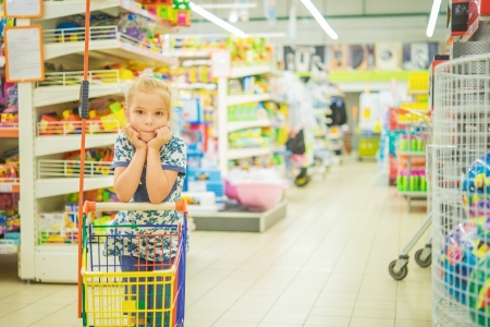 Little beautiful girl in modern supermarket with cart. photo