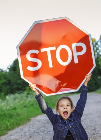 Beautiful little girl screaming and holding red sign STOP.