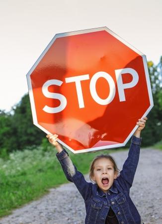 """ni�os sosteniendo un cartel: Hermosa ni�a gritando y la celebraci�n cartel rojo """"STOP""""."""