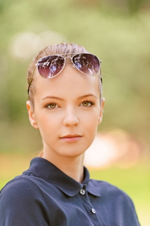 Portrait of calm beautiful young woman in sunglasses, against green of summer park. photo