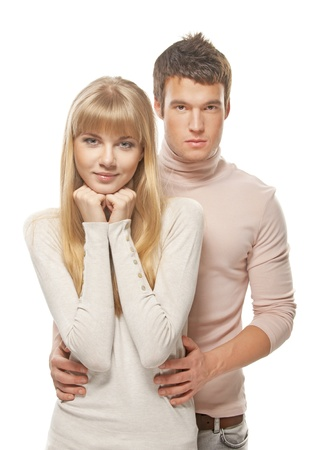 russian woman: Two young people: smiling blonde woman and serious dark-haired man embracing against white background.