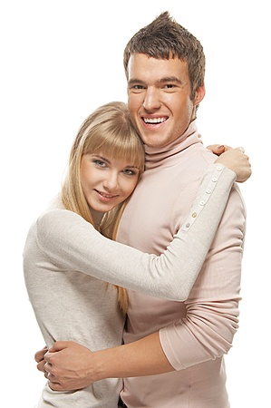 Two young people: smiling blonde woman and dark-haired man embracing against white background. photo