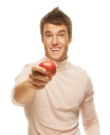 Portrait of young handsome dark-haired man wearing beige jersey, holding red apple against white background.