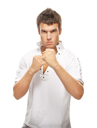 Close-up portrait of young dark-haired man holding fists in front of his face against white background.