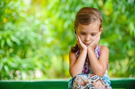 shy: Little girl on a green lawn leans against chair and thinks of mother.