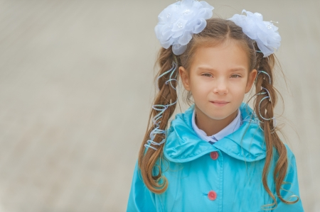 tresses: Little smiling beautiful girl with bows in blue cloak. Stock Photo