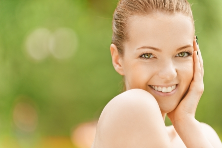 eye close up: Portrait of smiling beautiful young woman with bare shoulders, against green of summer park. Stock Photo
