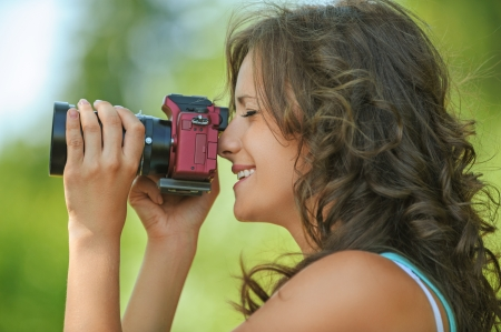 shootting: portrait young charming long-haired curly woman holding hands camera background outdoors Stock Photo