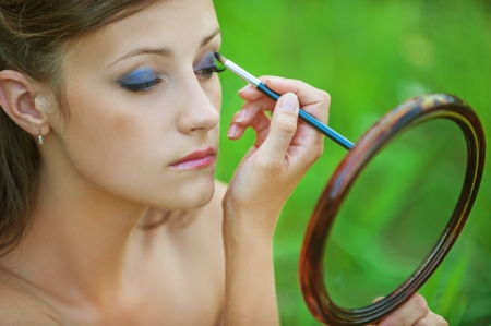 ravishing: Close-up portrait of young beautiful brunette woman colouring her eyelid and looking in mirror at summer green park.