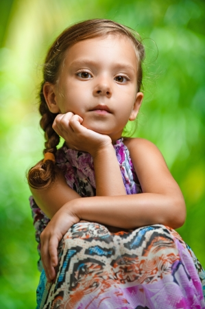 portrait of young, cute girl sitting on wooden table in long dress, against background of summer green park photo