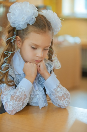 Beautiful little first grader sad about table. Stock Photo - 22096757