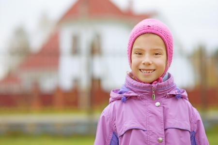 tresses: Portrait of smiling beautiful little girl in pink hat and jacket on red background of house. Stock Photo
