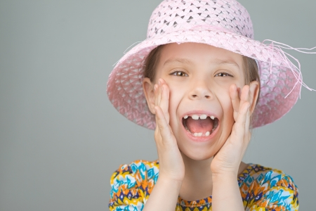 bawl: Beautiful young girl shouts loud voice, on gray background. Stock Photo
