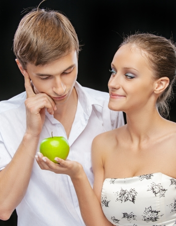 funny fruit: portrait of beautiful smiling brunette girl giving apple to confused happy guy on black