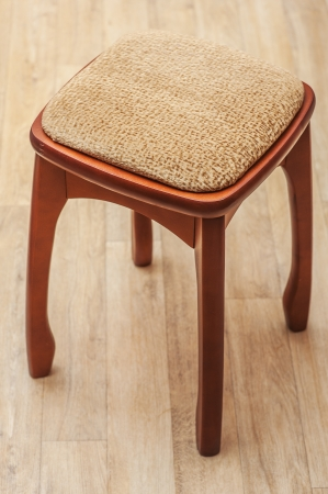 Wood chair with upholstered seat is on parquet floor. photo