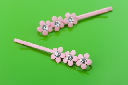 barrettes: Two pink barrettes are on green glossy table. Stock Photo