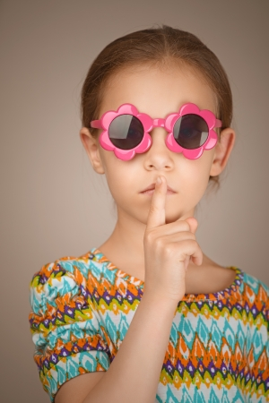 Beautiful sad little girl puts index finger to lips, on brown background. photo