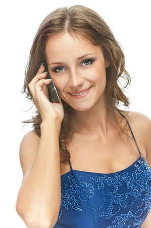 Charming girl in blue dress speaks by phone, isolated on white background. photo
