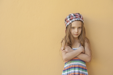 girl in red dress: Beautiful little girl in dress and cap against pink wall. Stock Photo