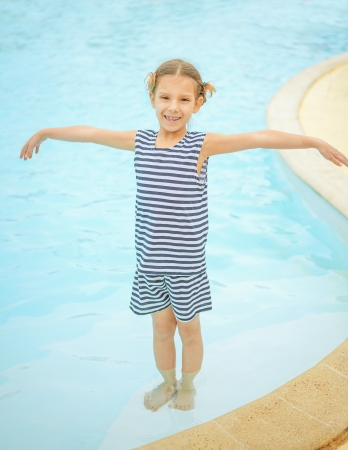 Beautiful little girl in pool water park. photo