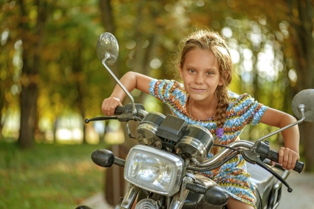 Little beautiful cheerful girl on old bike in park. photo
