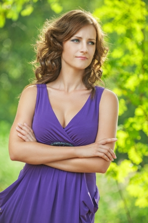 Beautiful young woman in purple dress thought, against green of summer park  photo