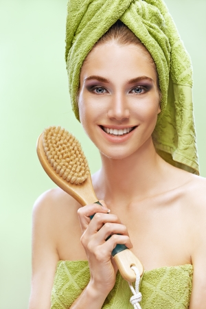 Beautiful young woman with brush of bath towels and green. photo