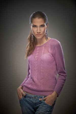 Portrait of smiling charming girl in pink sweater, isolated on dark background. photo