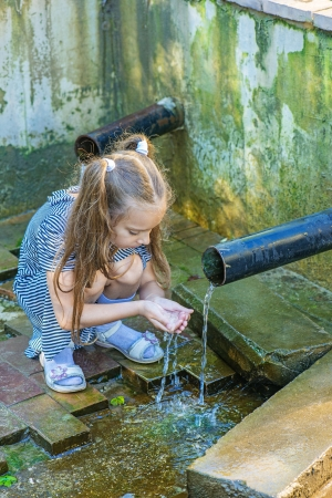 Little beautiful girl drinks water from source in summer city park. photo