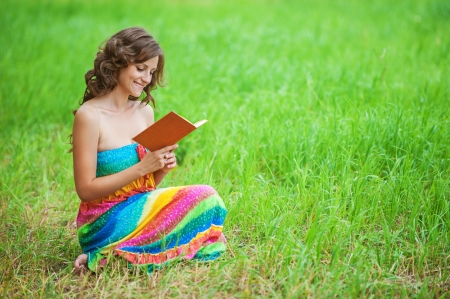 ravishing: Portrait of young attractive beautiful dark-haired curly woman wearing orange sweater and holding book at summer green park.