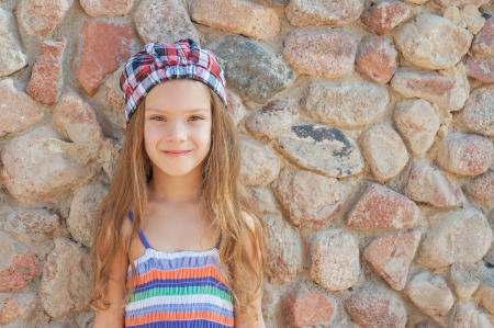 Portrait of smiling beautiful little girl in hat on background of wall. Stock Photo
