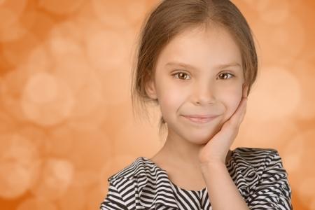 Close-up portrait of beautiful smiling young girl, on orange background. photo