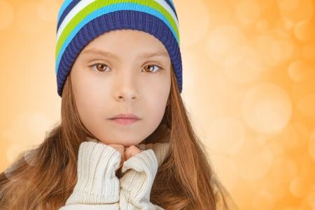petite fille triste: Belle petite fille triste en bonnet tricoté, sur fond jaune.