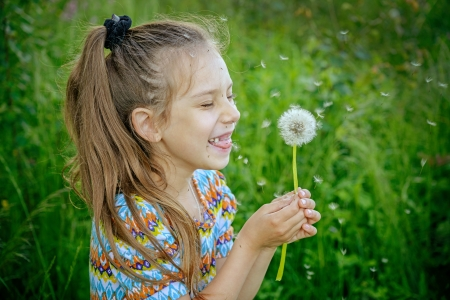 girl blowing: Beautiful little laughing girl blowing on white dandelion in green summer park.