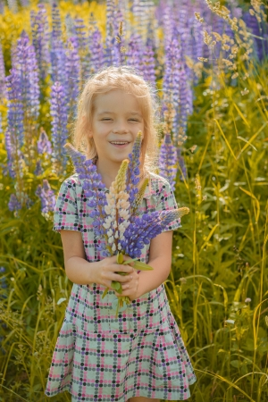 Beautiful smiling little girl walks on blossoming meadow in late summer. photo