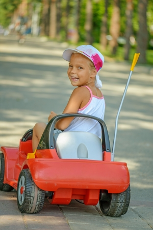 Beautiful little girl riding toy car in summer city park. photo