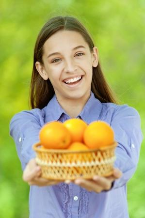 Smiling teenage girl holding basket of oranges, against green of summer park. photo