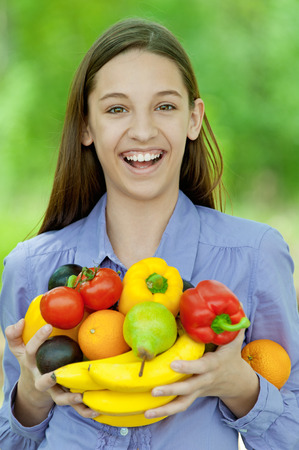 Smiling teenage girl holding banana, peppers, pears and oranges, against green of summer park. photo