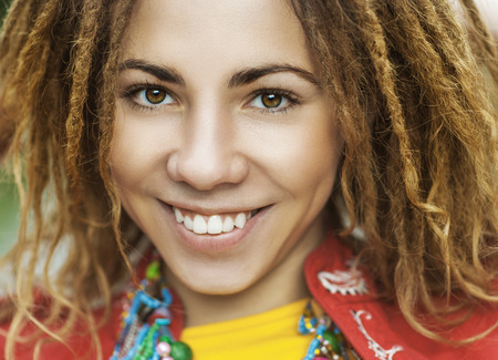 Young smiling beautiful woman with dreadlocks in red clothes closeup. photo