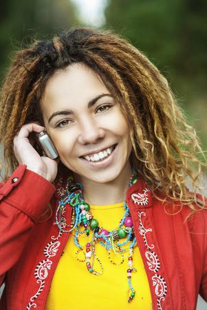 dreadlocks: Hermosa mujer sonriente joven con rastas en el vestido rojo hablando por teléfono móvil. Foto de archivo