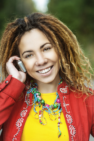 dreadlock: Young smiling beautiful woman with dreadlocks in red dress talking on mobile phone.