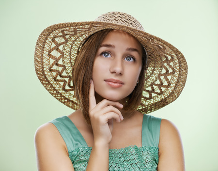 chapeau de paille: Portrait de sourire belle jeune femme en robe verte et chapeau de paille.