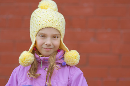 Portrait of smiling beautiful little girl in yellow hat and pink jacket on background of wall. photo