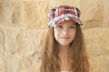 russian hat: Portrait of smiling beautiful little girl in hat on background of wall. Stock Photo