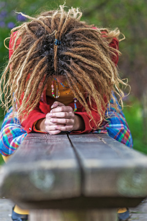 Young beautiful woman with dreadlocks in red clothes sitting on bench and crying.