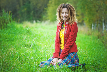 Young smiling beautiful woman with dreadlocks in red clothes sitting in park on grass. photo